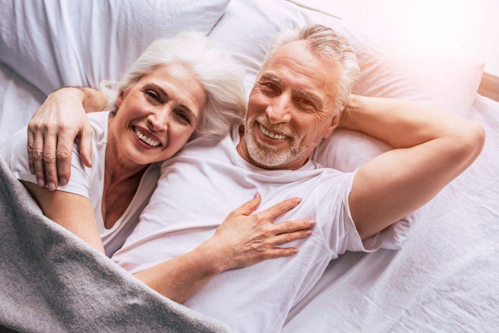 Imagem de um casal de idosos (homem e mulher) deitados na cama. Ele abraça a mulher e os dois sorriem muito, Estão felizes. Ambos usam camiseta branca e estão cobertos com uma manta cinza clara.