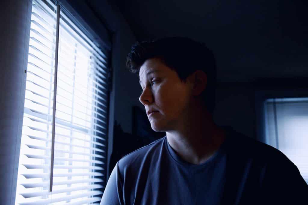 Mulher em um quarto escuro olhando para janela triste