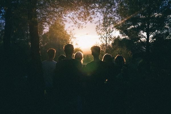 Pessoas de costas em floresta olhando para o sol ao fundo refletindo