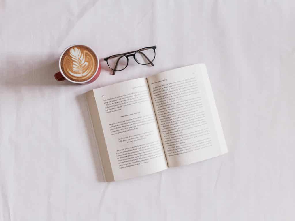 Livro aberto em uma superfície branca, ao lado está um óculos e uma caneca com café espumoso.