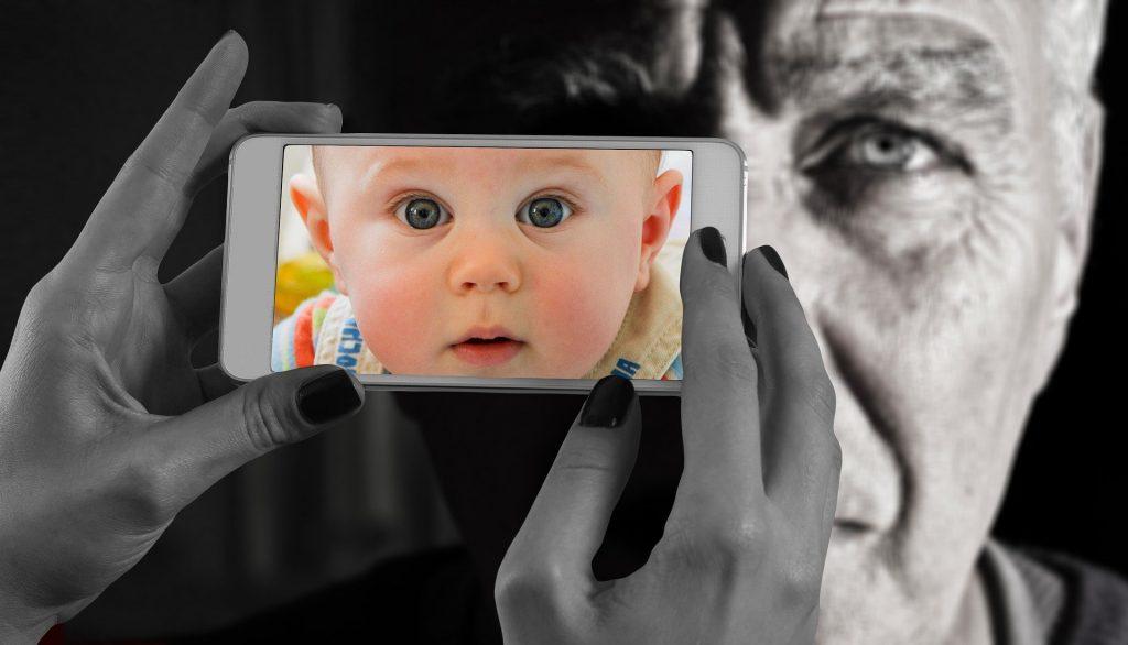 Imagem do rosto de um senhor. Mulher segura um celular e na imagem do celular é refletida a imagem de um bebê.