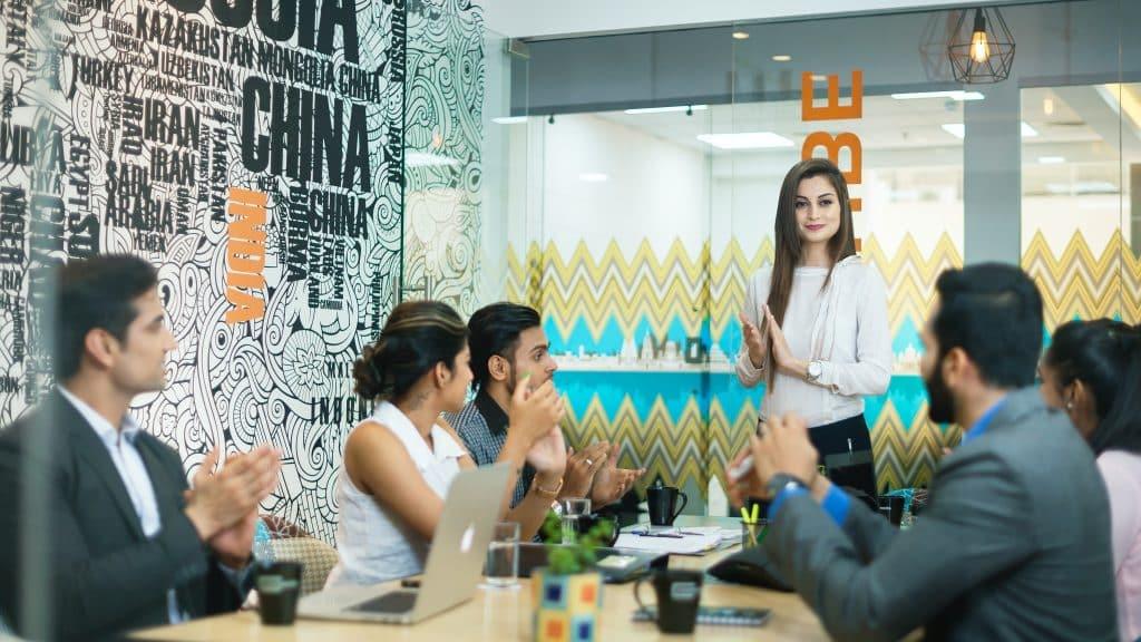 Mulher falando em pé em um escritório com outras pessoas aplaudindo