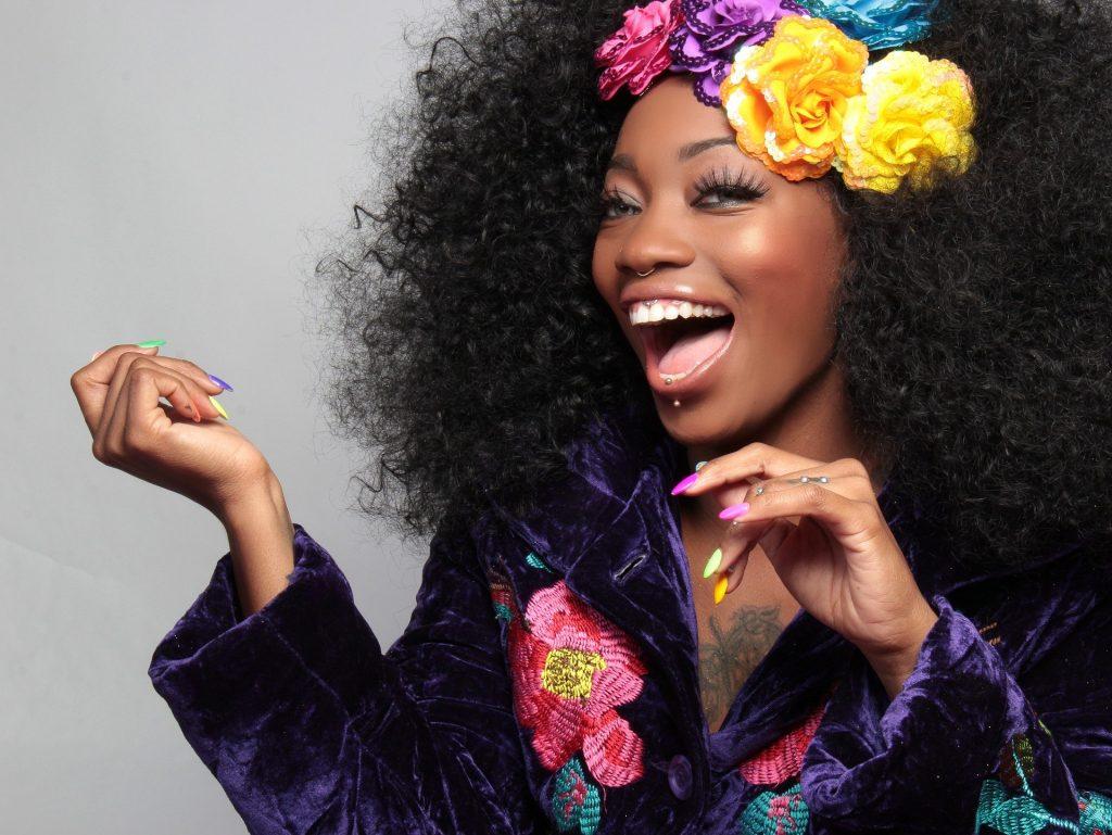 Imagem de uma linda mulher negra. Ela está muito feliz e sorri mostrando os seus lindos dentes brancos. Ela usa uma blusa de frio roxa bordada com flores. Seu cabelo também está enfeitado com grandes flores coloridas.