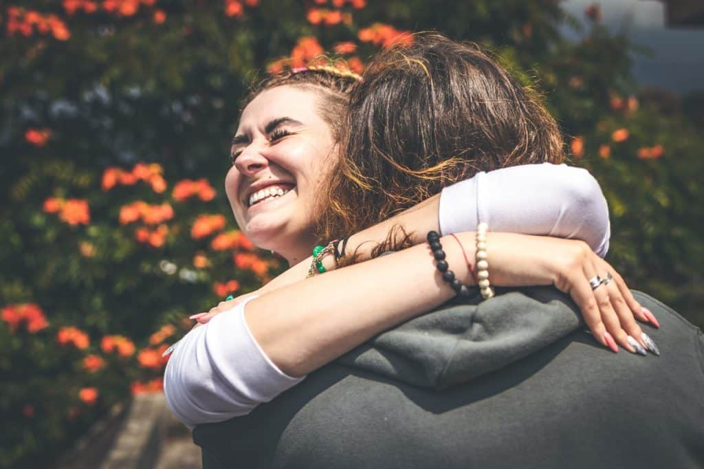 Mulher abraçando pessoa de costas para a câmera, e sorrindo.