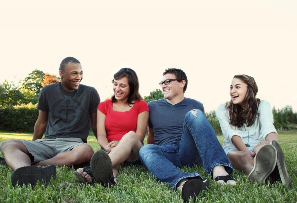 Grupo de quatro pessoas sentadas lado a lado em um gramado, todos sorriem.