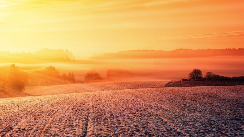 Imagem de um campo coberto com neve. Ao fundo o por do sol com raios refletindo sobre a neve.