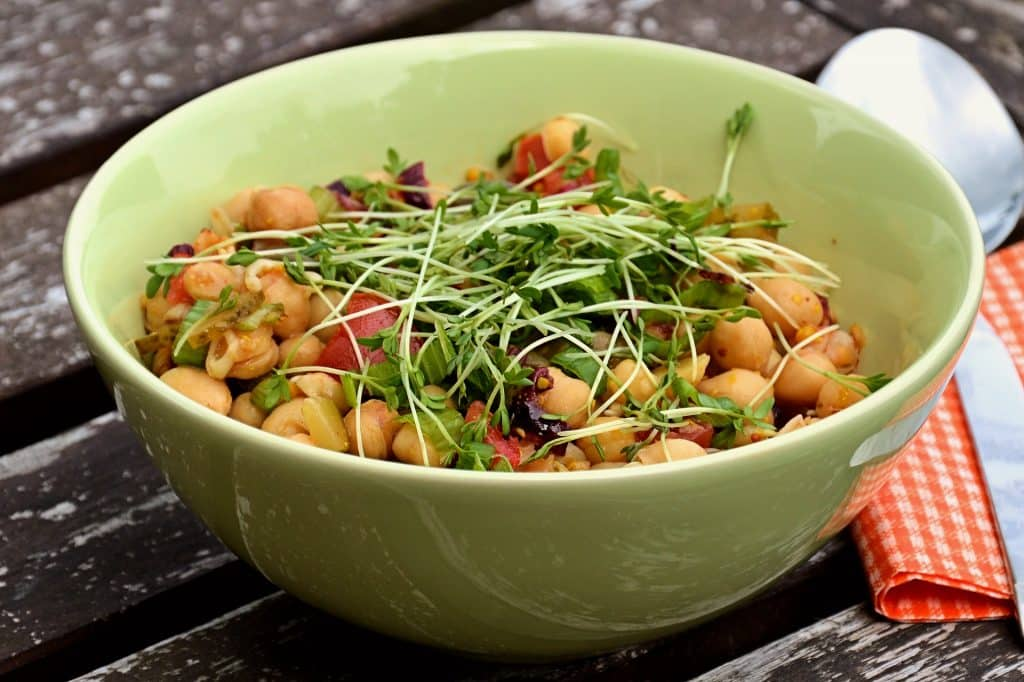 Imagem de uma bowl de porcelana na cor verde clara cheia de salada de grão de bico.