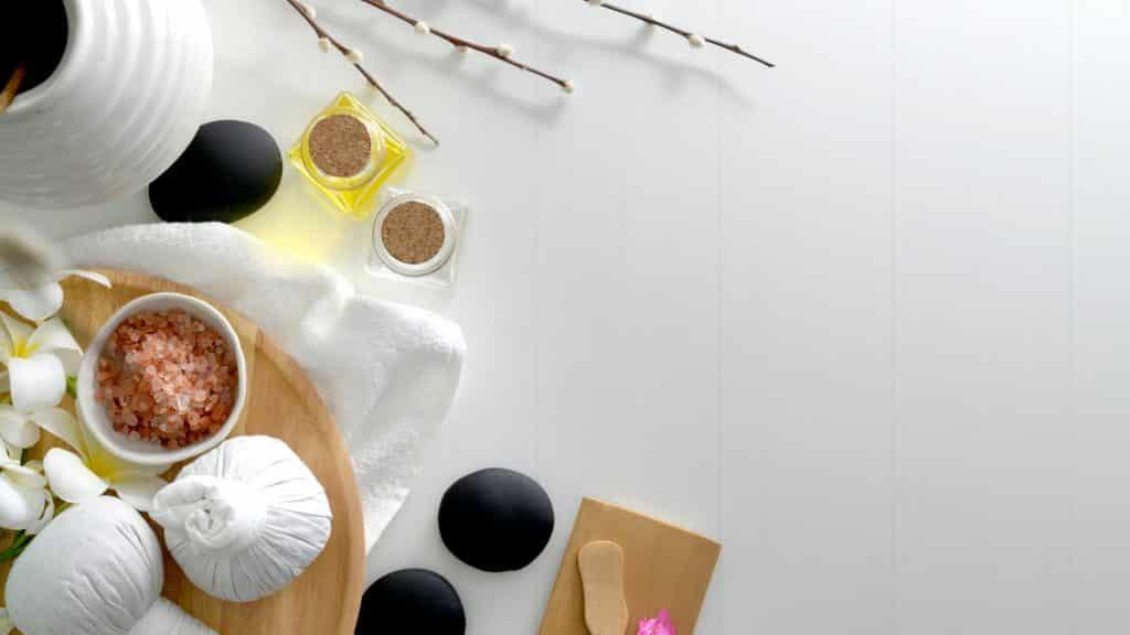 Utensílios de massagem sobre uma mesa, com óleos, massageadores e sais de banho.