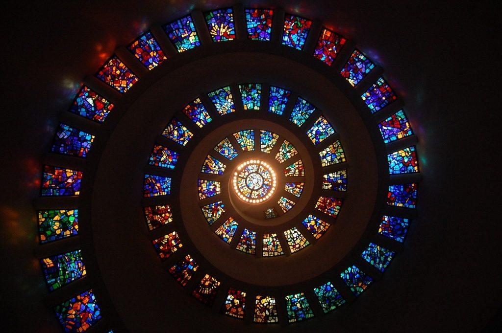 Parte interna de uma cúpula, com uma espiral guiando até seu topo. Essa espiral é formada por vitrais retangulares e coloridos.