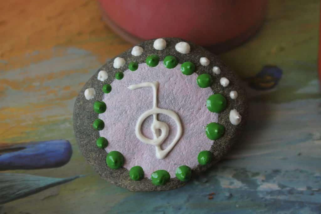 Imagem de uma pedra de cura usada na aplicação do Reiki. Ela é pintada com pontinhos branco e verde. Ao centro uma símbolo da cultura.