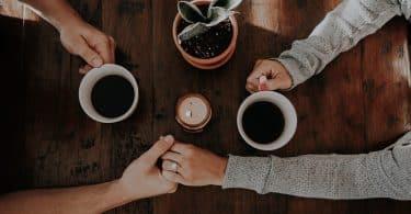 Casal com as mçaos juntas e com a outra mão segurando um café
