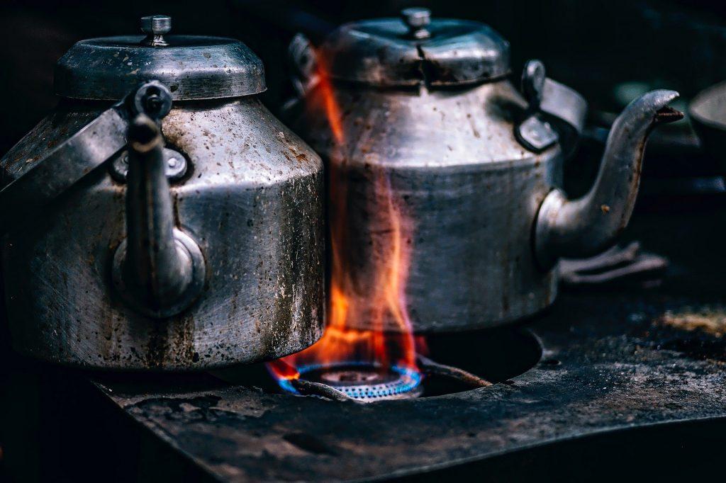 Imagem de duas chaleiras de alumínio cheias de quentão. Ela estão sobre um fogão aceso.