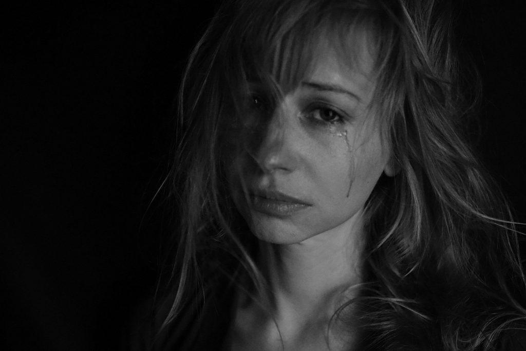 Imagem em preto e branco de uma mulher de cabelos longos. Ela está triste e chora muito.