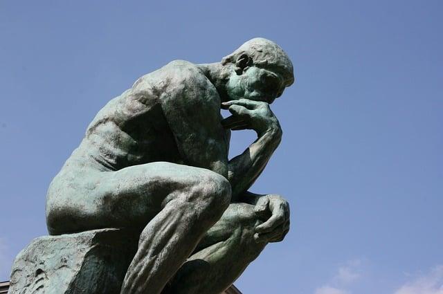 Estátua de Pensador com céu azul ao fundo