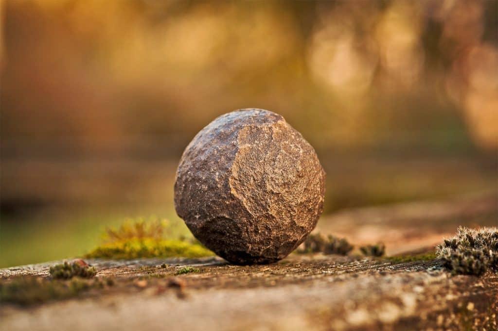 Foto de uma rocha redonda parada no chão.