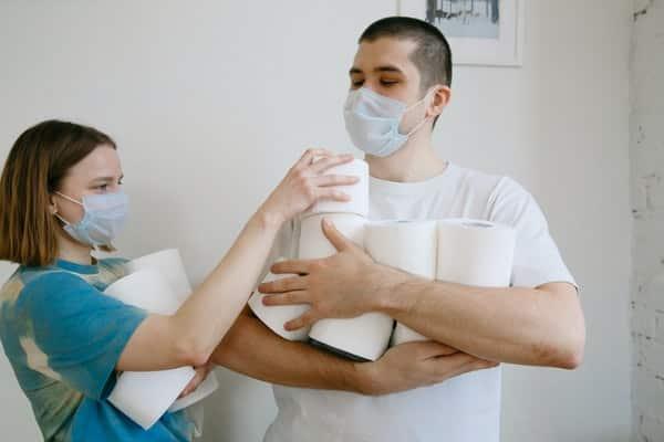 Casal segurando rolos de papel higiênico com máscaras no rosto