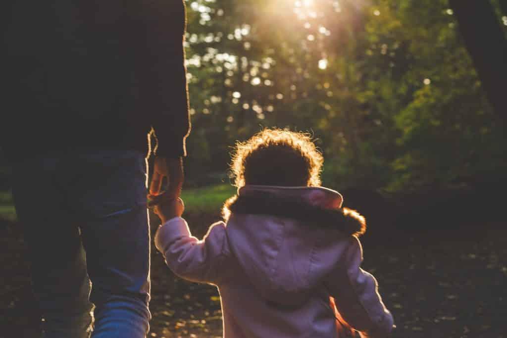 Menina criança andando de mãos dadas com seu pai por um parque.