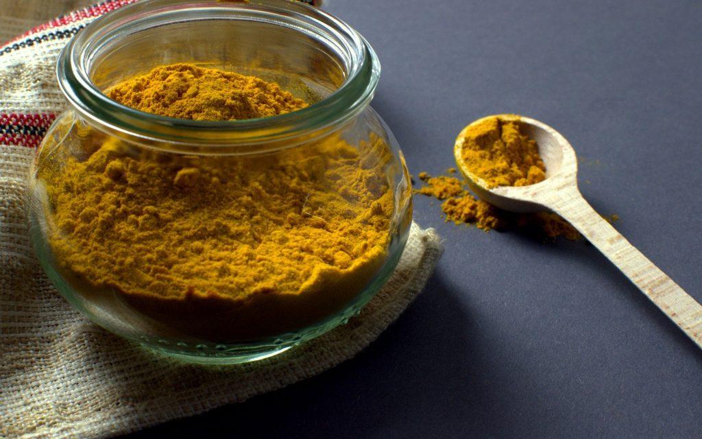 Imagem de pó de cúrcuma em um recipiente de vidro. Ao lado uma colher de madeira com um pouco do pó que será usado em uma receita natural de remédio para vitiligo.