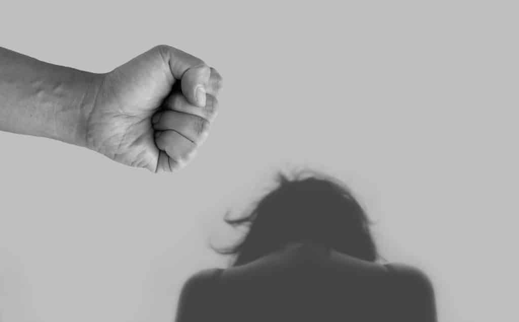 Imagem em preto e branco de uma mulher de costas cabisbaixa e sobre ela a mão de um homem pronto para dar um golpe de murro sobre ela.