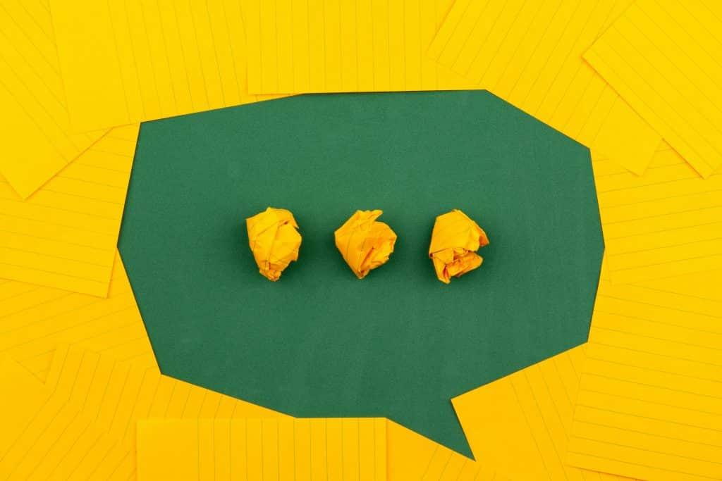 Balão de conversa com reticências no meio feitos de bolinhas de papel