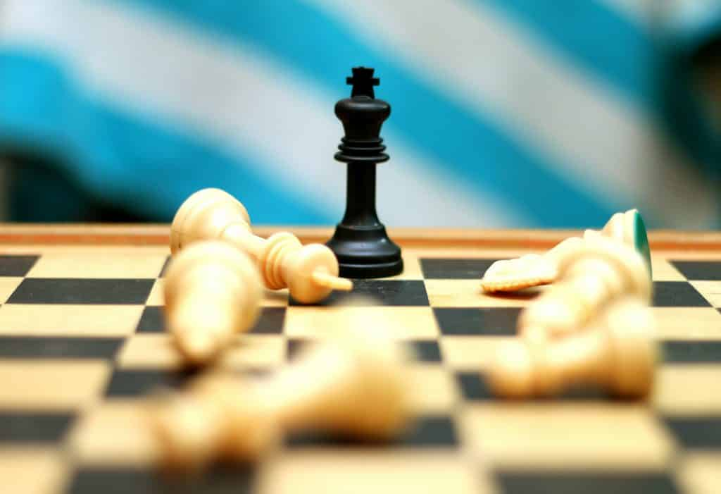 Tabuleiro de xadrez com várias peças derrubadas e apenas uma em pé.