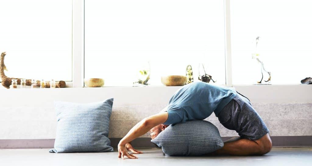 Homem fazendo yoga na sala de sua casa.