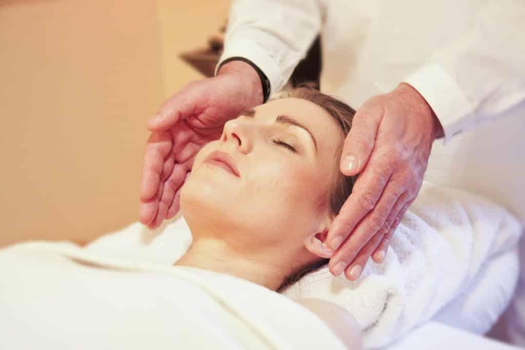 Mulher deitada sobre um lençol branco. Ela está com os olhs fechados recebendo um tratamento de reiki de um homem.