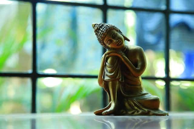 Imagem pequena de Buda apoiado em joelho