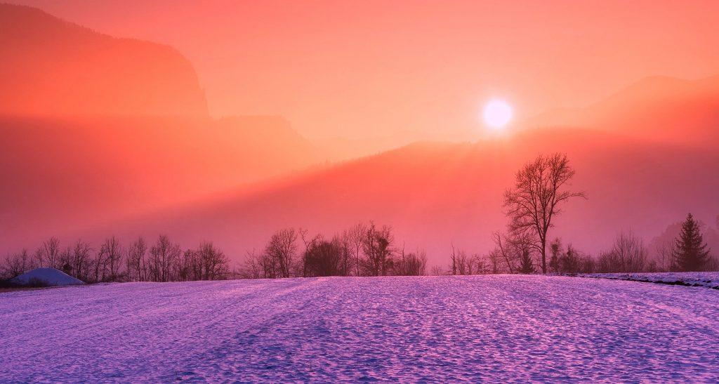 Imagem do inverno. Rua coberta de gelo. Ao fundo uma montanha com o nascer do Sol.