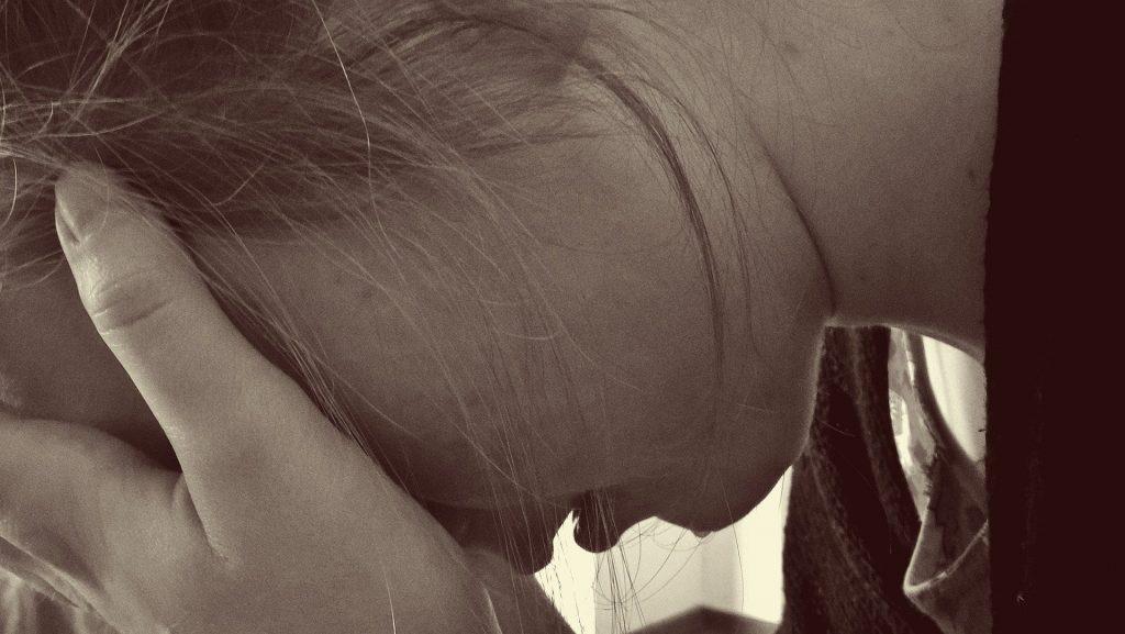 Imagem em preto e branco de uma mulher cabisbaixa com as duas mãos sobre o rosto. Ela está desesperada pois sofreu violência doméstica.