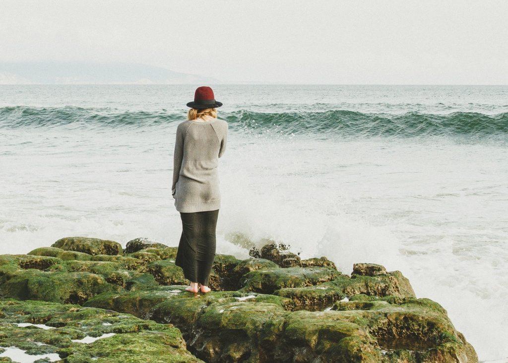Imagem de uma mulher olhando para frente do mar em  uma tarde fria de outono. Ela veste saia longa e um cardigan cinza e um chapéu na cor vermelha.