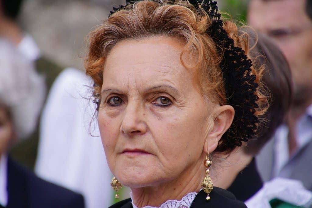 Imagem do rosto de uma senhora. Ela está com o cabelo preso e usa uma tiara de renda na cor preta e um longo brinco dourado.