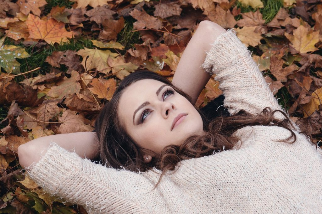 Imagem de uma linda mulher deitada sobre um chão forrado de folhas de outono. Ela está pensativa e olhando para o céu.