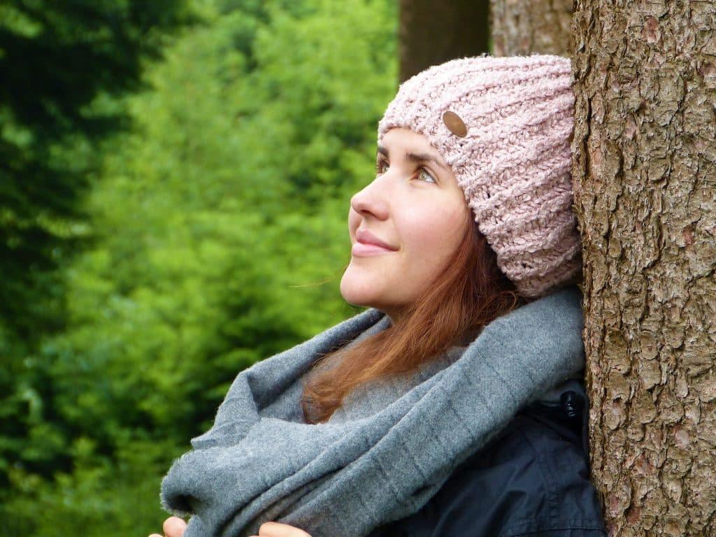 Imagem de uma jovem mulher em uma floresta. Ela está encostada em uma árvore. Está com a fisionomia alegre e relaxada. Ela usa uma trouca de lã rosa e um cachecol cinza.