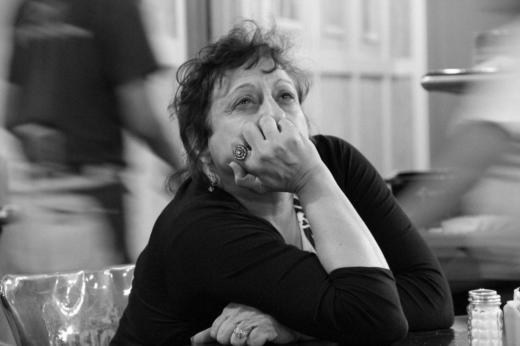 Imahem em preto e branco de uma senhora de meia idade. Ela está com cabelos presos e um olhar triste.