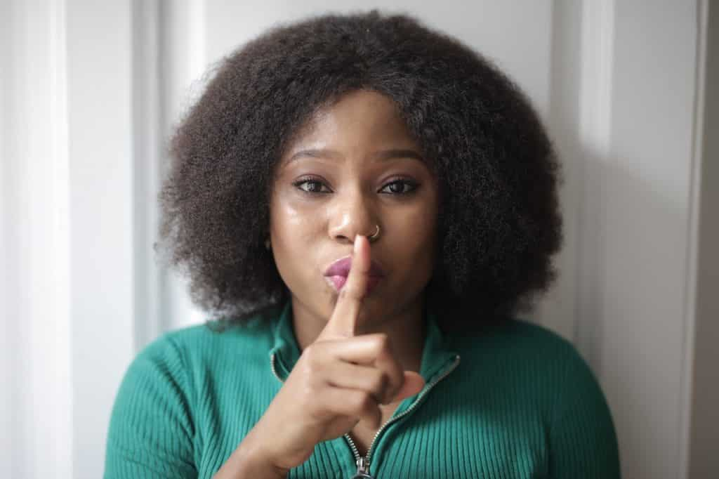 Mulher com um dedo indicador na frente dos lábios, indicando silêncio. Seus lábios estão em formato de beijo e ela olha diretamente para a câmera.