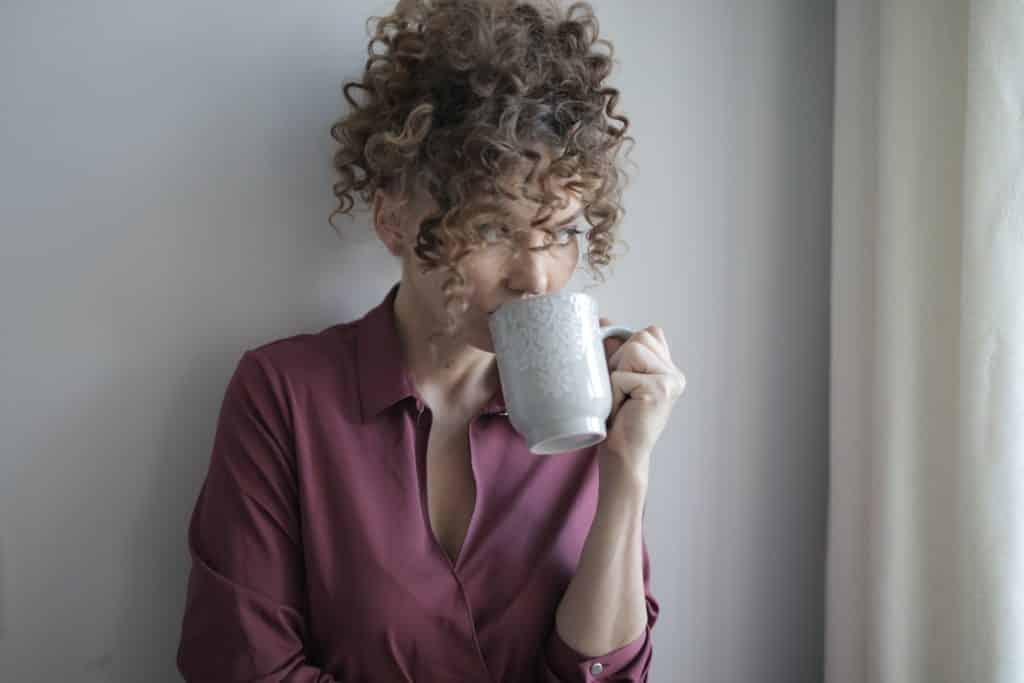 Mulher de cabelos cacheados bebendo em uma caneca.