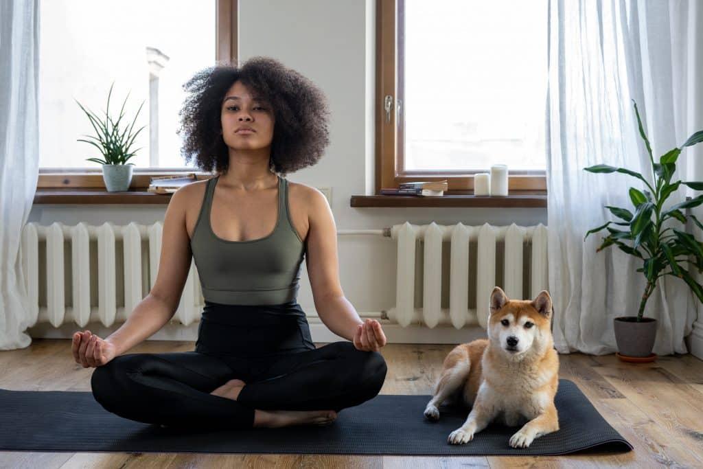 Mulher de cabelos cacheados sentada no chão da sala, ao lado de seu cachorro, meditando.