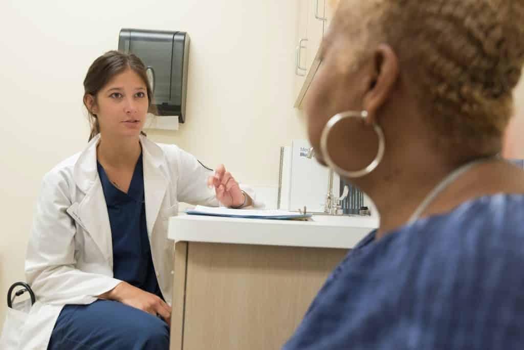 Médica conversando com paciente em consultório.