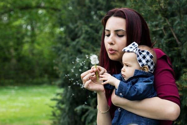 Mãe segurando filha e assoprando flor dente-de-leão