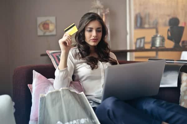 Mulher sentada fazendo compras online com o notebook e cartão na mão