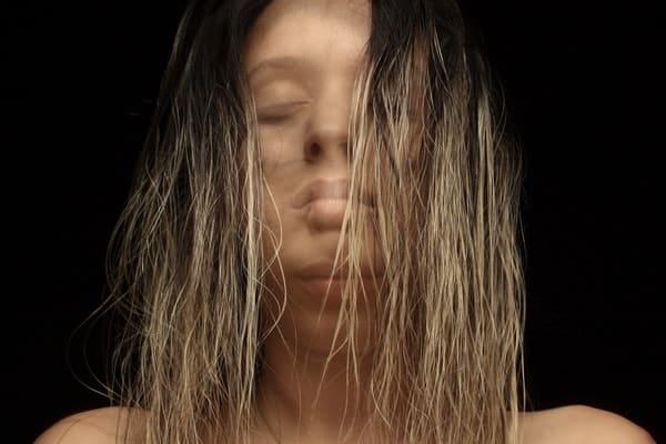Mulher com rosto em movimento e imagem sobreposta a outra
