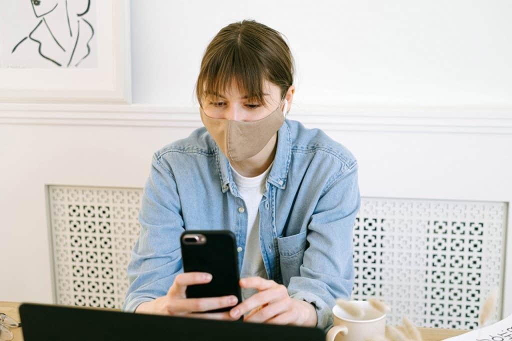 Mulher usando máscara de proteção no rosto, enquanto digita em seu celular, em um ambiente fechado.