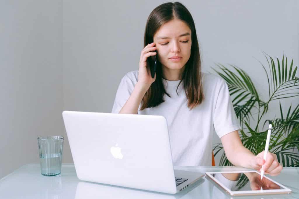 Mulher sentada em frente a um notebook e um tabet. Ela está falando em um telefone, e escrevendo no tablet com uma caneta.
