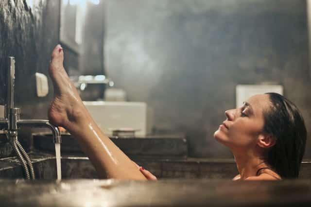 Mulher tomando banho em banheira com pé para cima