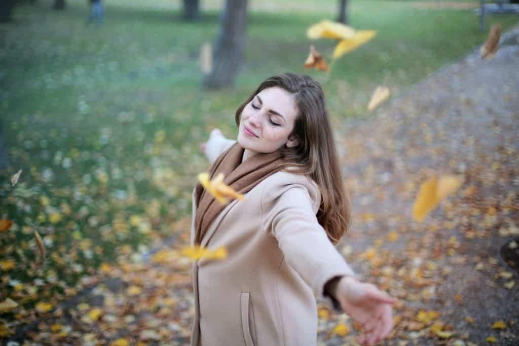 Mulher usando casaco, e girando com os braços abertos e sorrindo. Folhas secas caem, e outras já preenchem o chão.