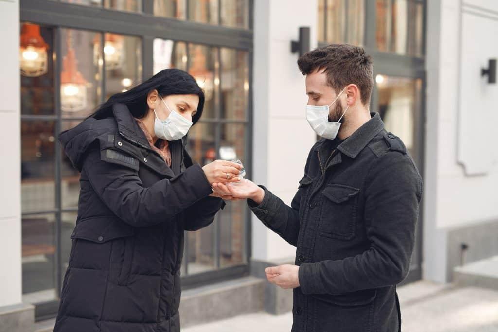 Mulher colocando álcool em gel nas mãos de um homem na rua, durante o dia, enquanto os dois usam máscaras de proteção descartáveis no rosto.