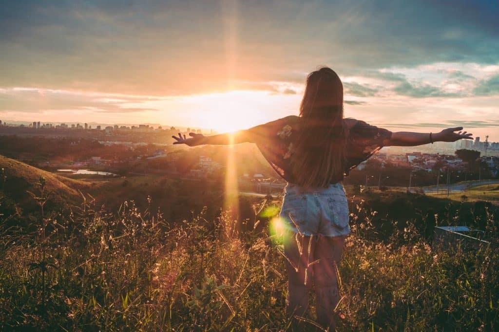 Mulher em um campo gramado, com os braços abertos para o pôr-do-sol.