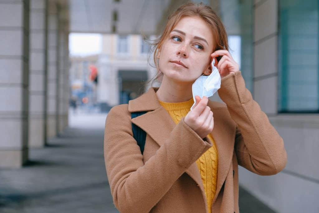 Mulher na rua retirando a máscara de proteção do rosto.