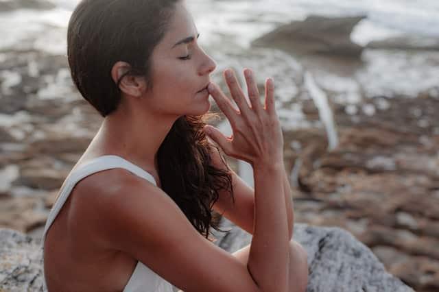 Mulher com mãos em frente ao rosto de olhos fechados em conexão